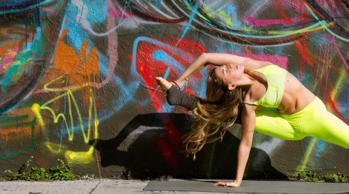 Yoga teacher in an urban environment doing a pose.